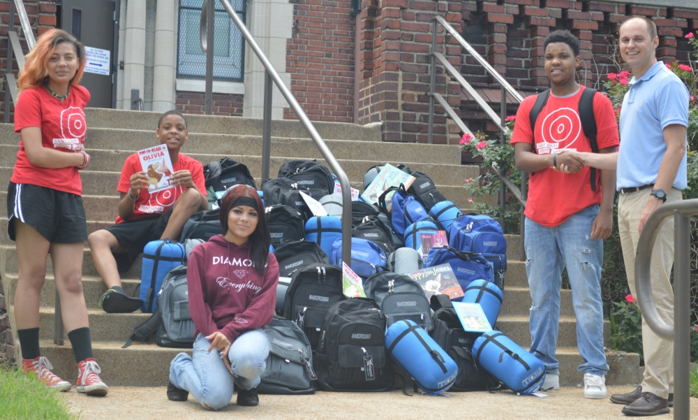 Teens deliver the resource backpacks to Principal Colby Heckendorn at Patrick Henry Downtown Academy Elementary School.