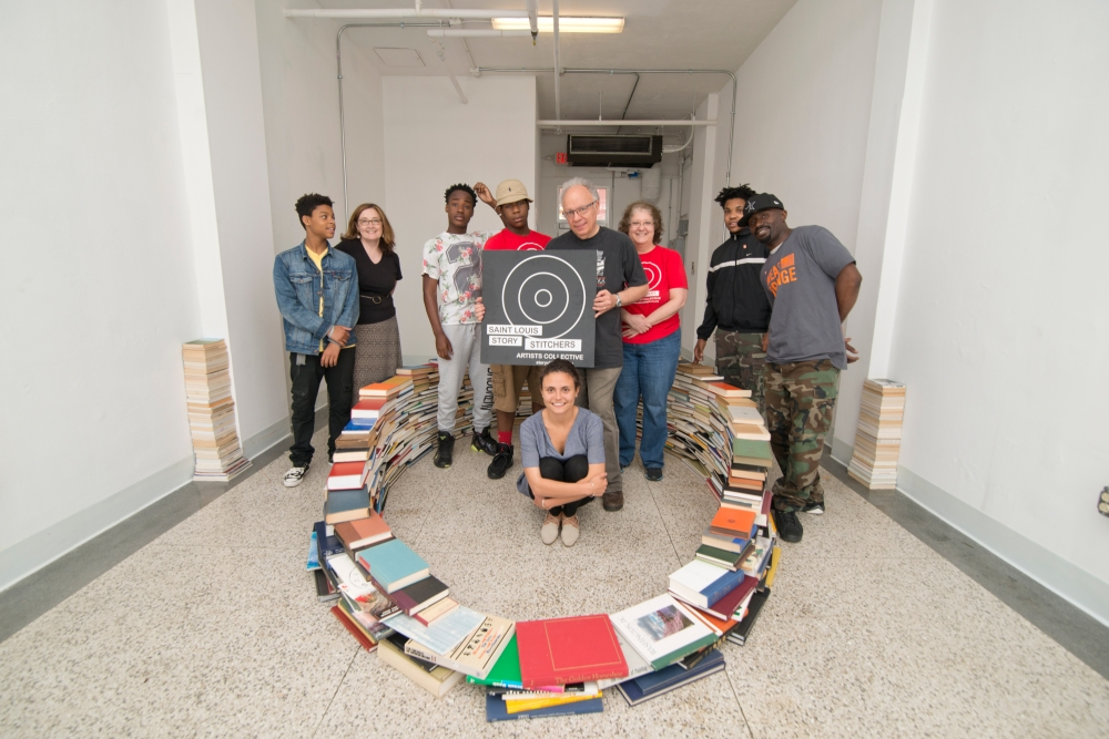 Buzz Spector, professor of art, leads teens and artists from Story Stitchers in creating one of his trademark book installation at the Story Stitchers Storefront Studio at 616 N. Skinker. (Photo: Danny Reise/WUSTL Photos)
