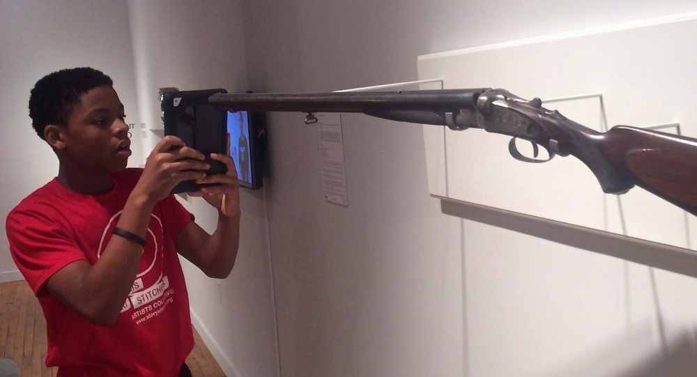 Stitchers Teen Council member Toryon investigates an artwork by Adam Mysock, created from a decommissioned gun in the exhibition, Guns in the Hands of Artists, Des Lee Gallery, Washington University in St. Louis, September 12, 2015.